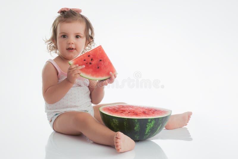 Neonata che mangia la fetta dell'anguria isolata su fondo bianco immagine stock