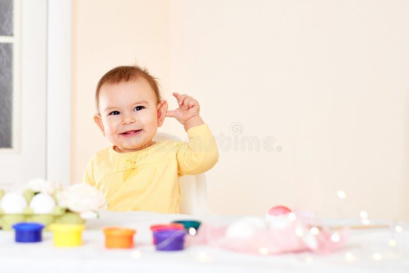 Neonata che si siede alla tavola ed al concetto felice sorridente di verniciatura di infanzia delle uova di Pasqua di festa fotografia stock