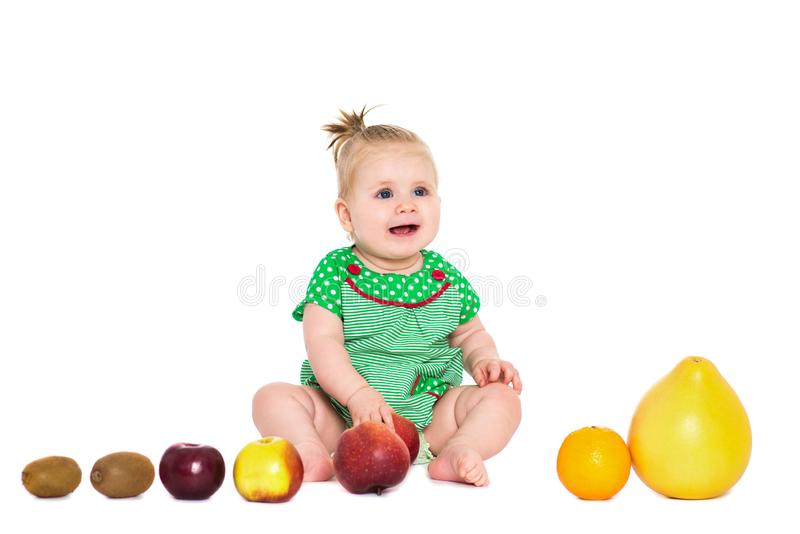 Neonata che si siede con la frutta e le verdure, isolate sopra bianco fotografia stock