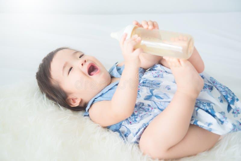 Neonata che tiene bottiglia per il latte ed i sorrisi sul letto fotografie stock