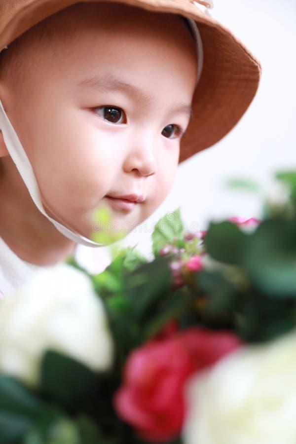 Neonata cinese adorabile con un odore del cappello dei fiori fotografia stock libera da diritti