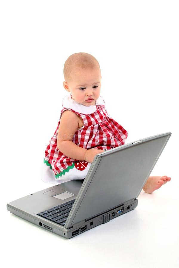 Neonata con il computer portatile sopra bianco fotografia stock