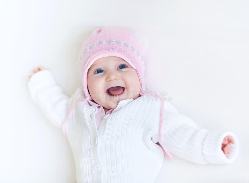 Neonata di risata divertente in maglione tricottato bianco immagine stock