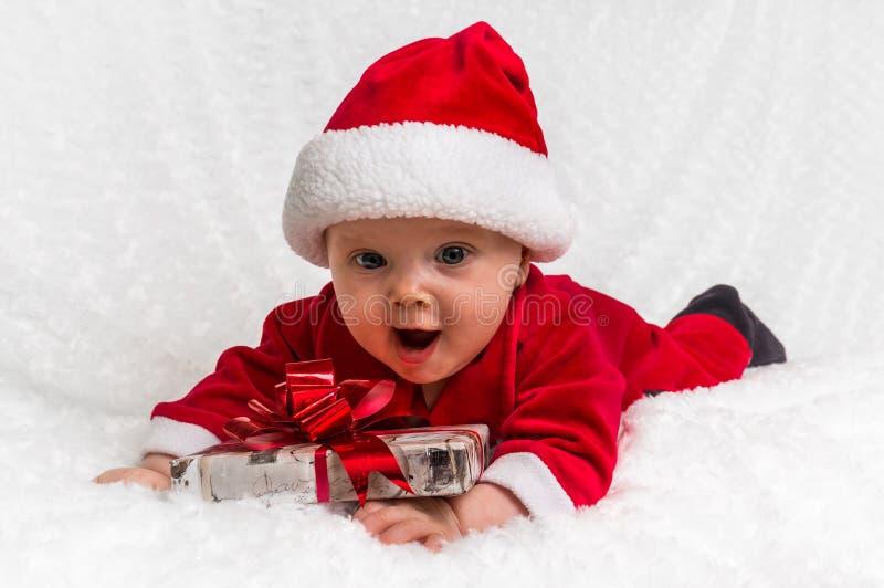 Neonata di Santa che si trova sulla coperta bianca con il regalo immagini stock