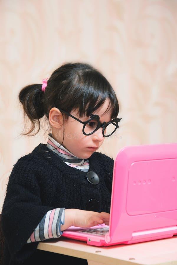 Neonata divertente dietro il computer portatile con i vetri fotografia stock