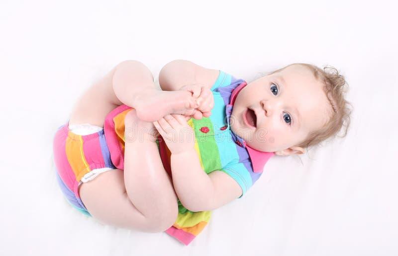 Neonata dolce in vestito a strisce variopinto che gioca con i suoi piedi fotografia stock