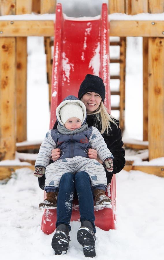 Neonata e madre divertenti sul campo da giuoco all'aperto nell'inverno fotografie stock