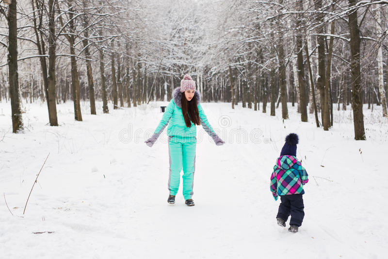 Neonata felice della tenuta della madre sulla passeggiata nella foresta nevosa di inverno fotografia stock libera da diritti