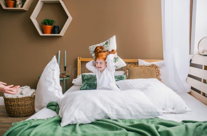 Neonata felice della testarossa che gioca a letto Bambina con il gioco rosso dei capelli sui pigiami d'uso del letto immagine stock