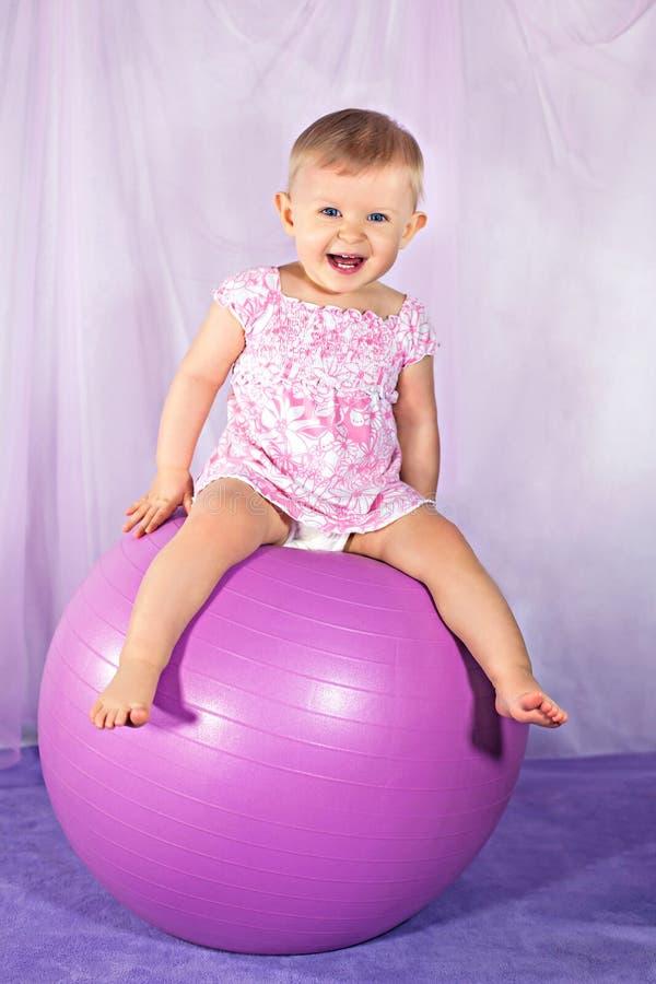 Neonata felice sulla palla fotografie stock
