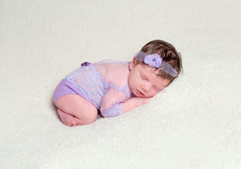 Neonata infantile in attrezzatura della viola del pizzo fotografie stock libere da diritti