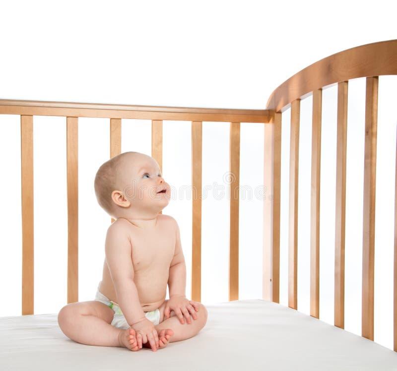 Neonata infantile del bambino in letto di legno che guarda giù sorridere felice immagine stock