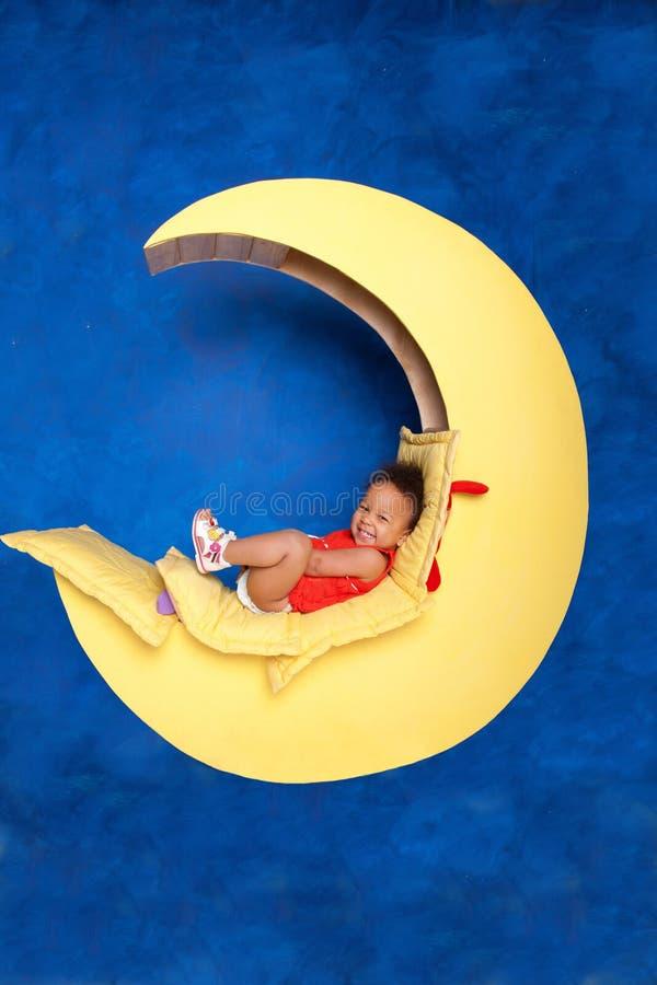 Neonata nera felice che si siede sulla luna immagini stock