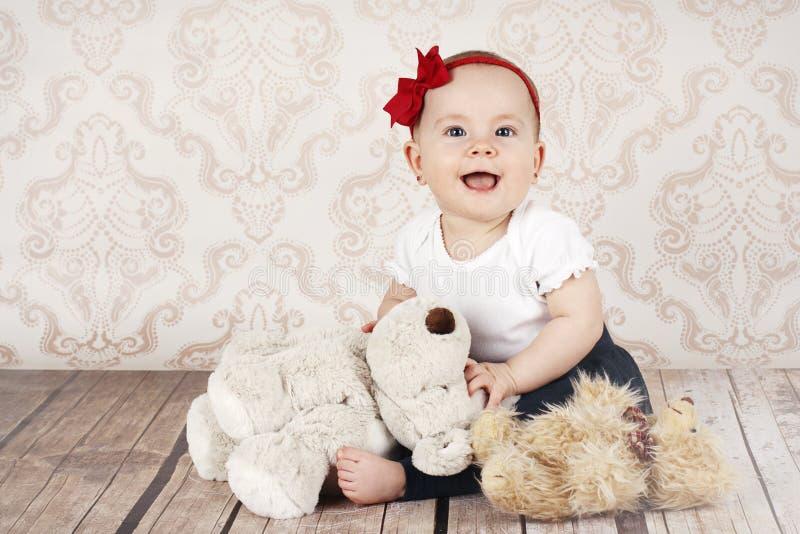Neonata piccola di risata con i giocattoli della peluche fotografia stock libera da diritti