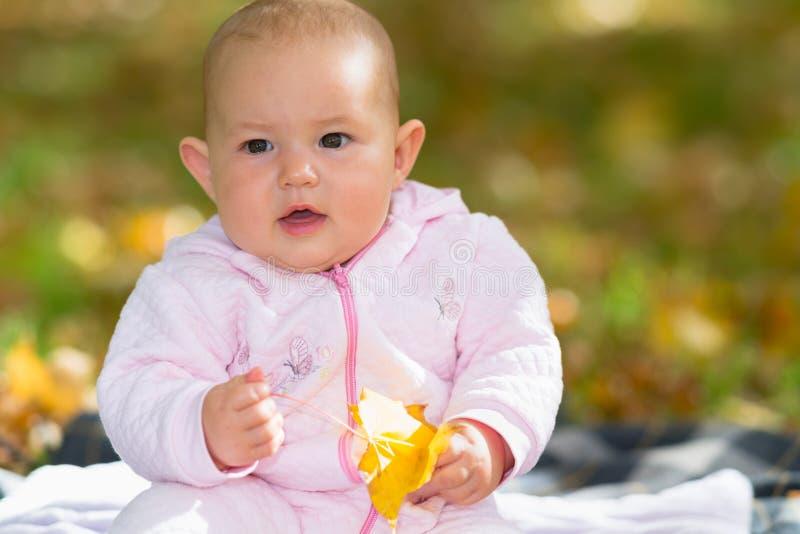 Neonata piccola graziosa che gioca con una foglia di caduta fotografie stock