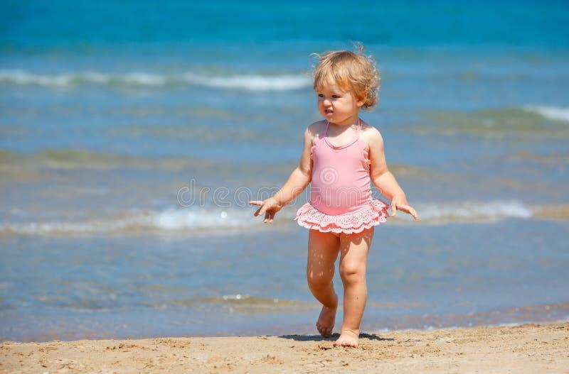 Neonata riccia sveglia che gioca su una bella spiaggia tropicale che porta un costume da bagno sveglio fotografia stock libera da diritti