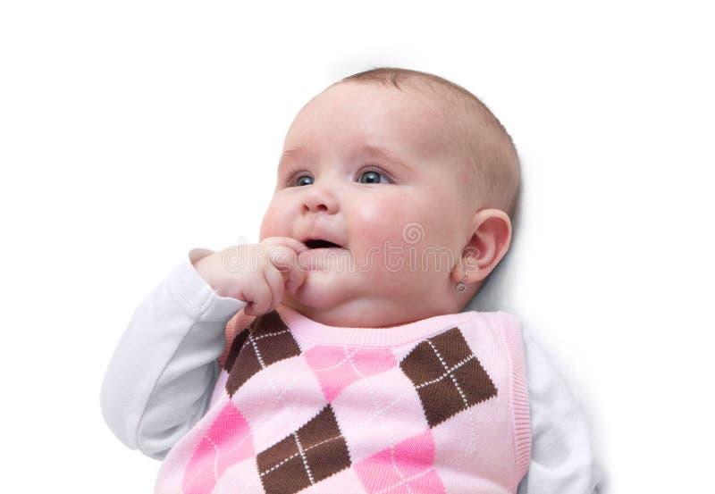 Neonata sorridente con il dito nella sua bocca Neonato femminile sveglio divertente vestito in maglione rosa isolato su fondo bia fotografia stock