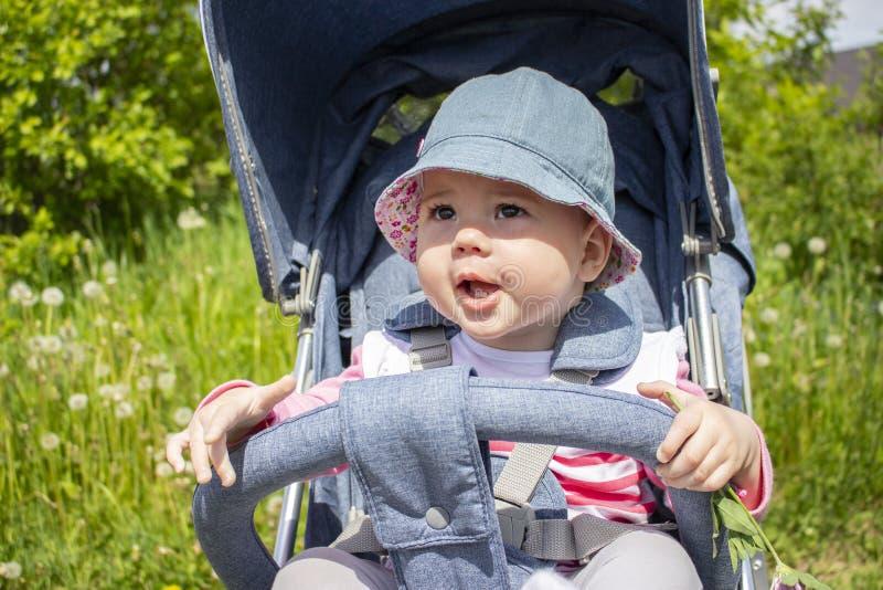 Neonata sorridente 9 mesi nelle passeggiate del Panama in un passeggiatore Ritratto di buon umore del primo piano del bambino fotografia stock libera da diritti