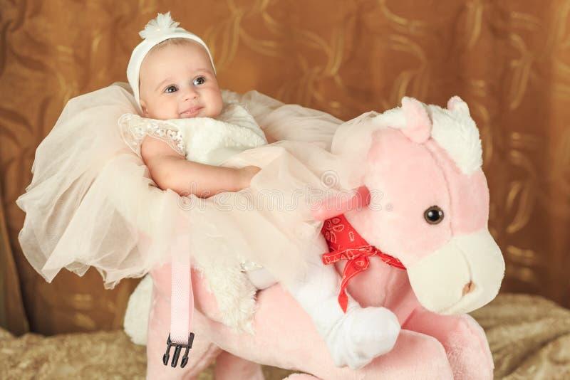 Neonata su un poney rosa fotografie stock libere da diritti