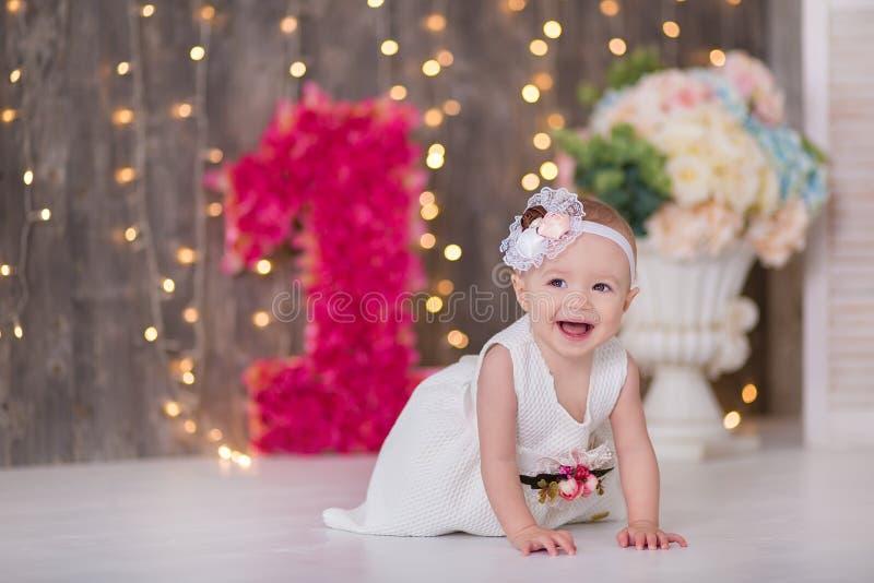 Neonata sveglia 1-2 anni che si siedono sul pavimento con i palloni rosa nella sala sopra bianco Isolato Festa di compleanno cele fotografia stock libera da diritti