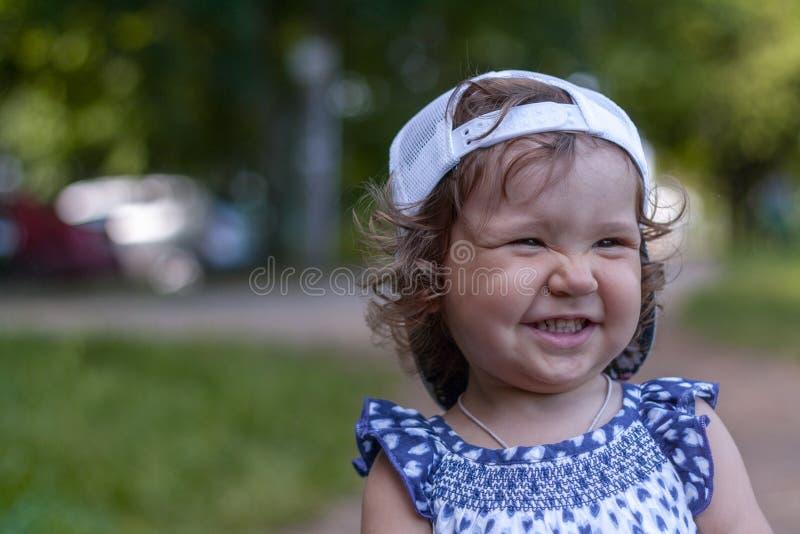Neonata sveglia in berretto da baseball, lustro con felicità, capelli ricci, sorriso incantante, ritratto soleggiato di estate fotografia stock libera da diritti