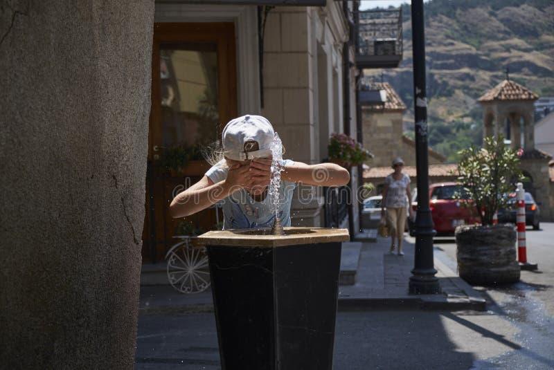 Neonata sveglia che beve dalla fontanella dell'acqua di estate immagine stock