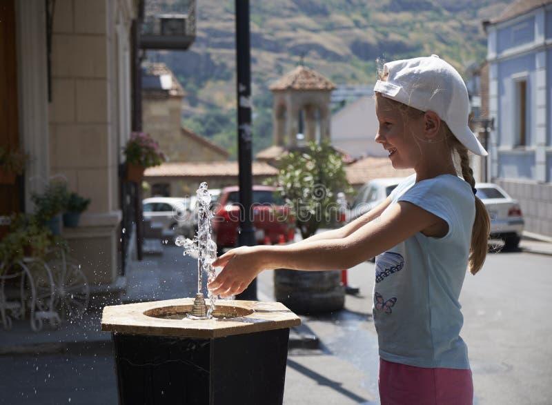 Neonata sveglia che beve dalla fontanella dell'acqua di estate fotografia stock