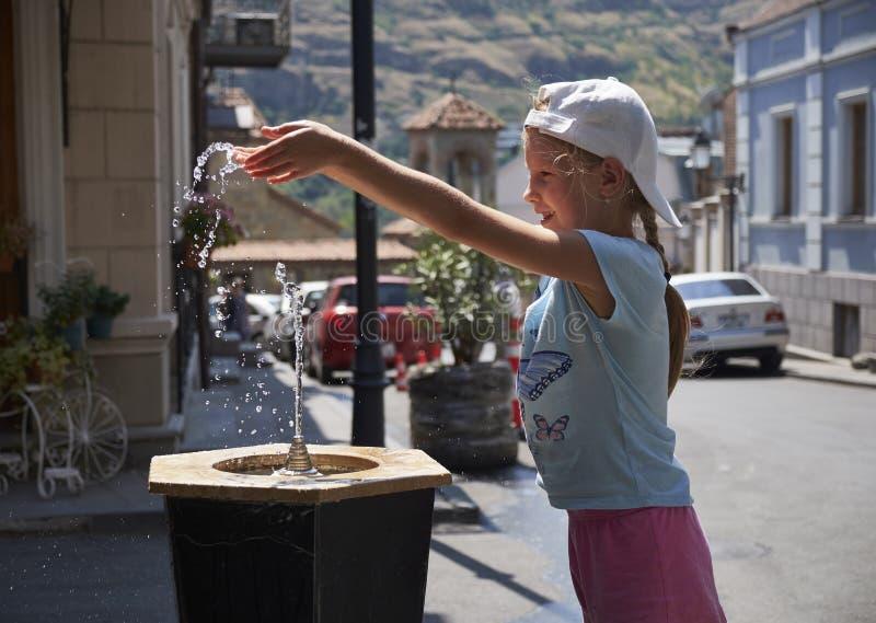 Neonata sveglia che beve dalla fontanella dell'acqua di estate immagini stock libere da diritti