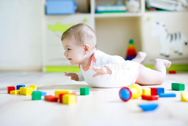 Neonata sveglia che gioca con i blocchi di legno variopinti fotografia stock libera da diritti