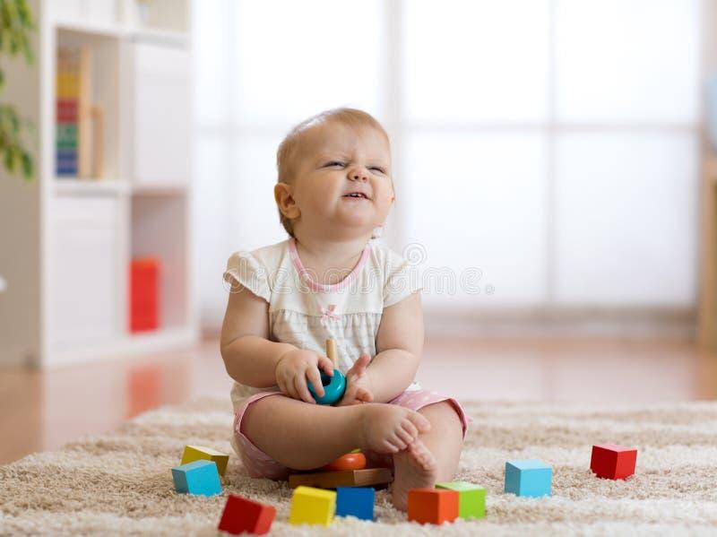 Neonata sveglia che gioca con i giocattoli in salone immagine stock