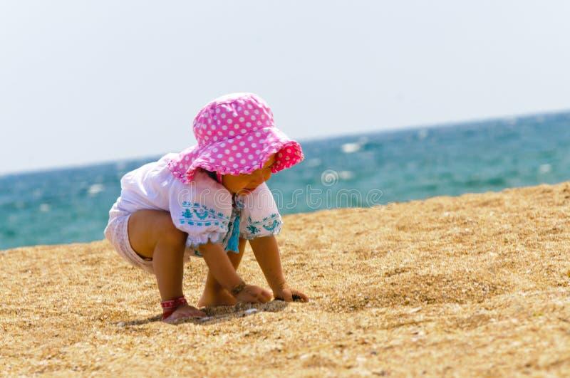 Neonata sveglia che gioca sulla spiaggia fotografie stock libere da diritti