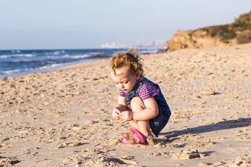 Neonata sveglia che gioca sulla spiaggia immagini stock libere da diritti