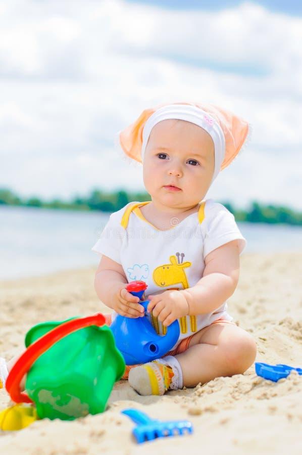 Neonata sveglia che gioca sulla spiaggia con la sabbia. fotografie stock libere da diritti