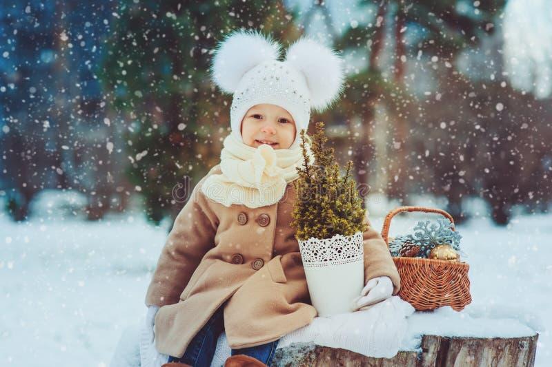 Neonata sveglia che gode della passeggiata di inverno in parco nevoso, cappello caldo d'uso fotografia stock