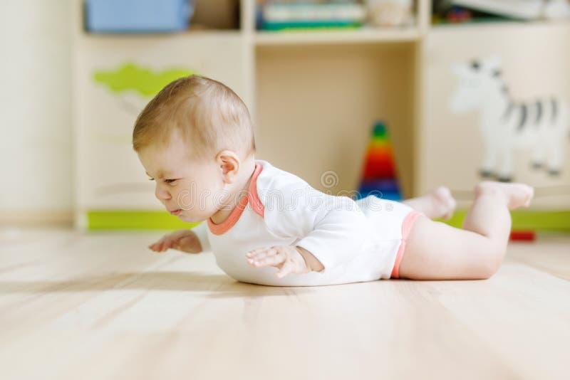 Neonata sveglia che impara strisciare e seduta nella stanza di bambini fotografie stock libere da diritti