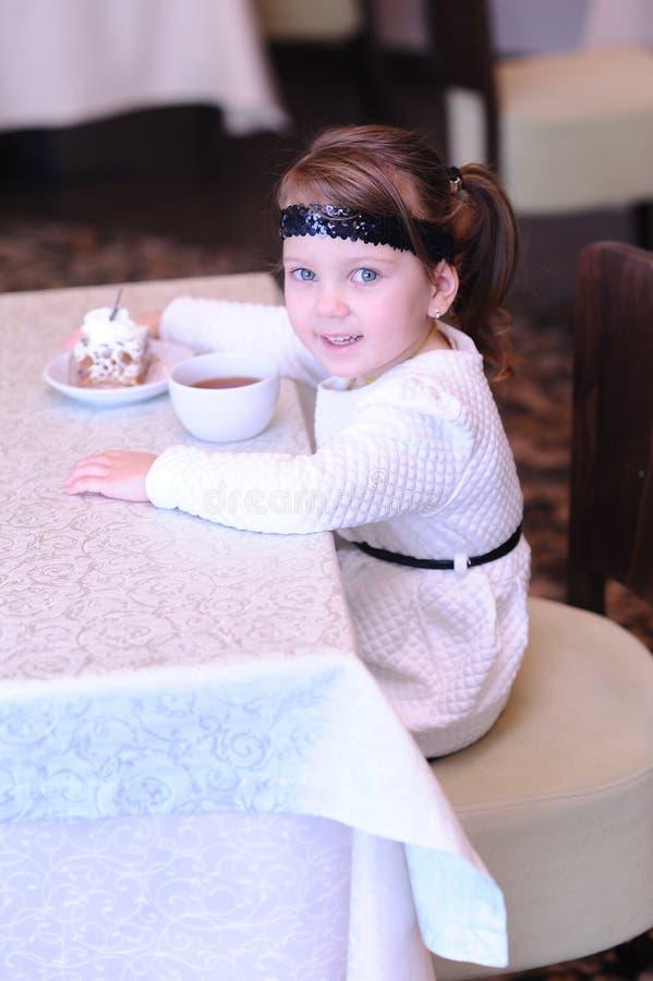 Neonata sveglia che tiene tazza di tè nero in caffè fotografie stock libere da diritti