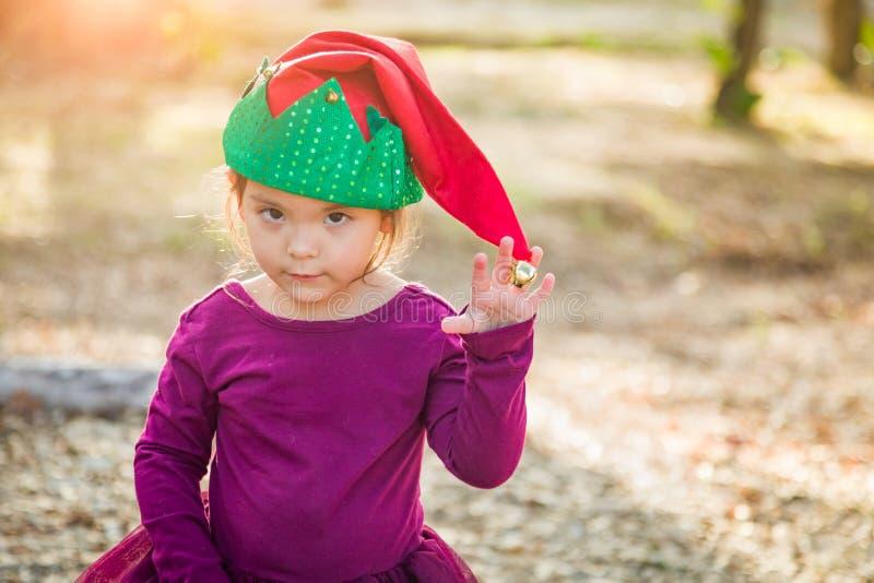 Neonata timida dei giovani della corsa mista divertendosi il cappello d'uso di Natale fotografia stock libera da diritti