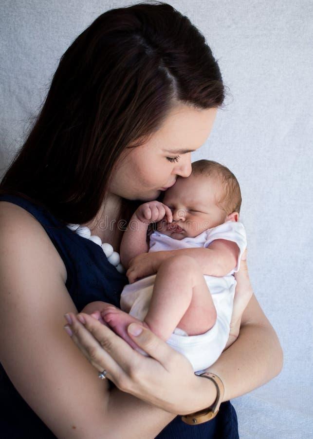 Neonato addormentato della tenuta della madre che bacia la sua fronte immagini stock libere da diritti