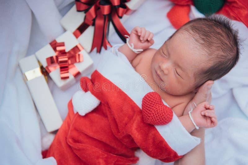 Neonato addormentato sulla mano della madre in cappello di Natale con il contenitore di regalo dal cuore del filato e di Santa Cl fotografie stock