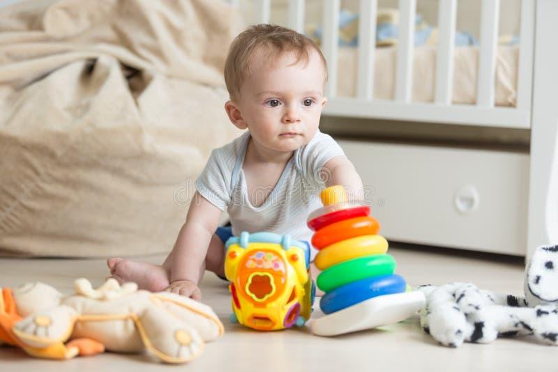 Neonato adorabile che gioca sul pavimento con le automobili variopinte, le torri ed i blocchetti del giocattolo fotografie stock libere da diritti