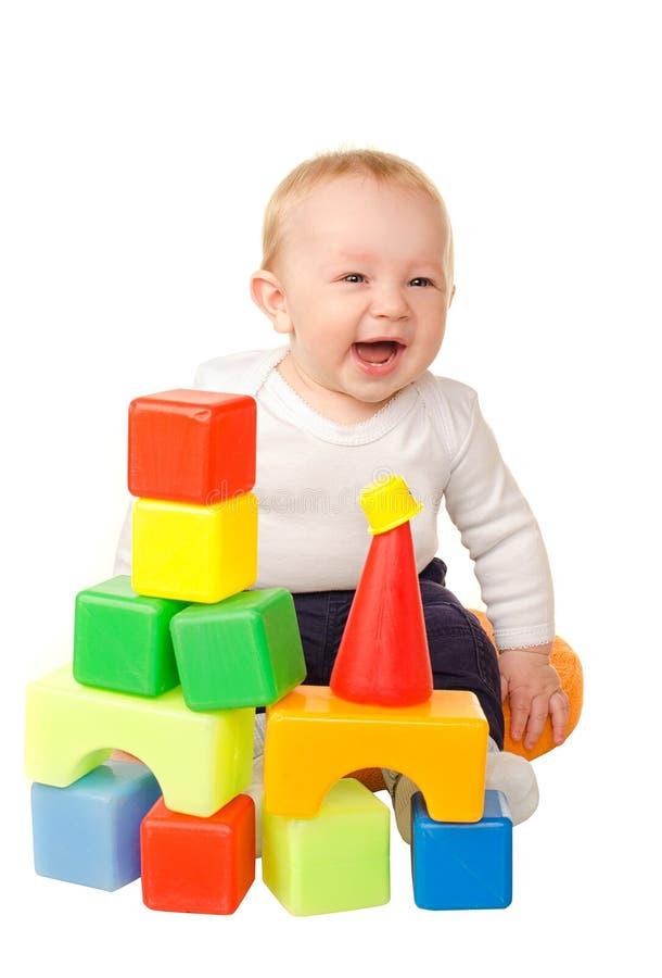 Neonato allegro che gioca con i blocchi variopinti fotografie stock libere da diritti