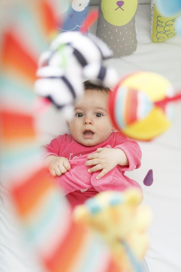 Neonato allegro che ride e che rispetta i suoi giocattoli in sua greppia immagine stock libera da diritti