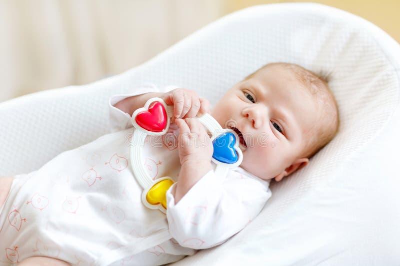 Neonato in buona salute sveglio che gioca con il giocattolo variopinto di crepitio in letto bianco a casa Bambino neonato, sguard fotografie stock libere da diritti