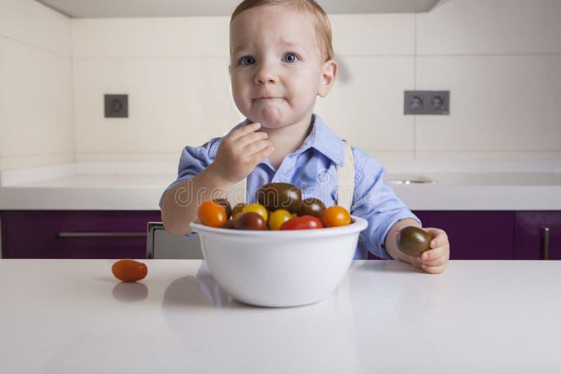Neonato che assaggia il tomatoe variopinto maturo della ciliegia immagini stock