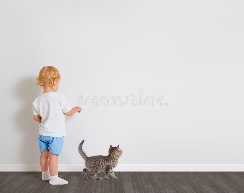 Neonato che attinge condizione della carta da parati di nuovo alla macchina fotografica con poco gatto fotografia stock libera da diritti