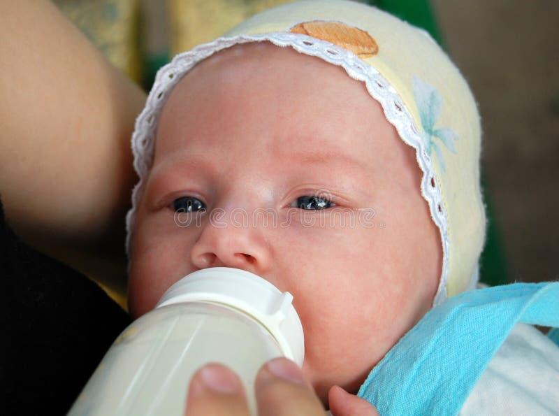 Neonato che beve dalla bottiglia di plastica fotografie stock