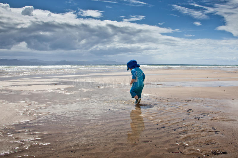 Neonato che cammina sulla grande spiaggia fotografia stock