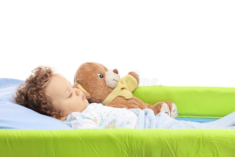 Neonato che dorme con il suo orsacchiotto in una culla immagini stock libere da diritti