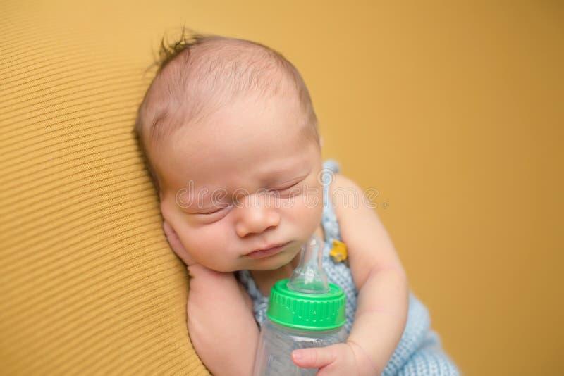 Neonato che dorme con la bottiglia immagine stock