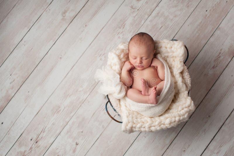 Neonato che dorme in un cesto metallico